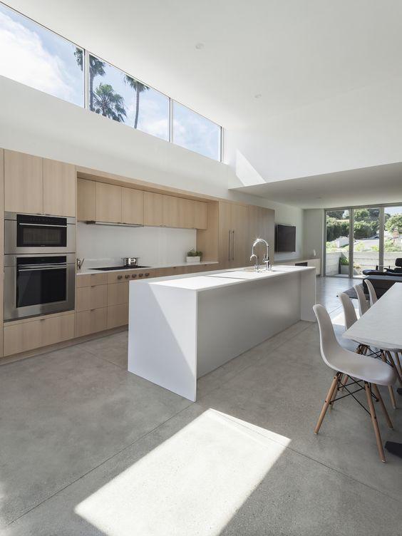 uno spazio minimalista con cucina e sala da pranzo, con mobili minimal, una parete vetrata e una finestra a lucernario per più luce qui