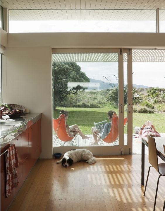 una moderna cucina abitabile con ante scorrevoli in vetro e finestre a lucernario che portano più luce all'interno e lo rendono più accogliente