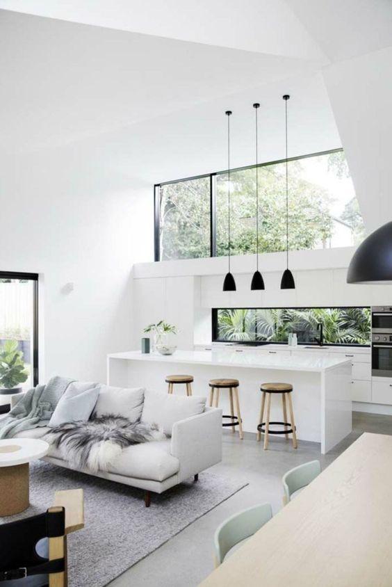 uno spazio tropicale minimalista in bianco e grigio, con tocchi neri per il dramma e con una grande finestra a lucernario per più luce