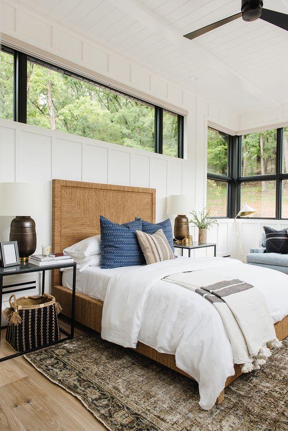 una moderna camera da letto colonica con una panca blu con cuscini, una grande finestra e una ulteriore lucernario