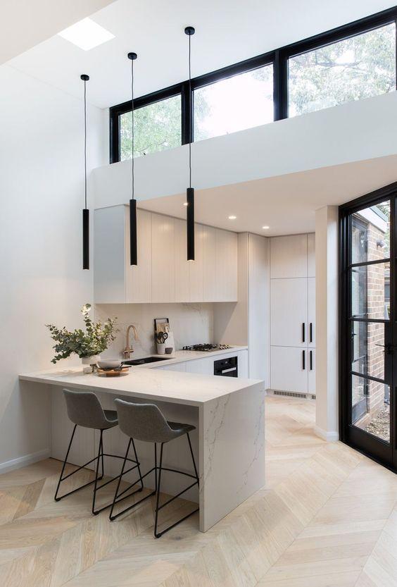 uno spazio minimalista in bianco e nero, con mobili minimalisti e lampade a sospensione nere più una finestra a lucernario sullo spazio