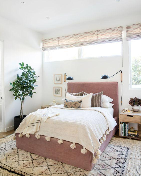 una camera da letto moderna con una finestra e una finestra a lucernario, un letto color malva e applique più una pianta in vaso
