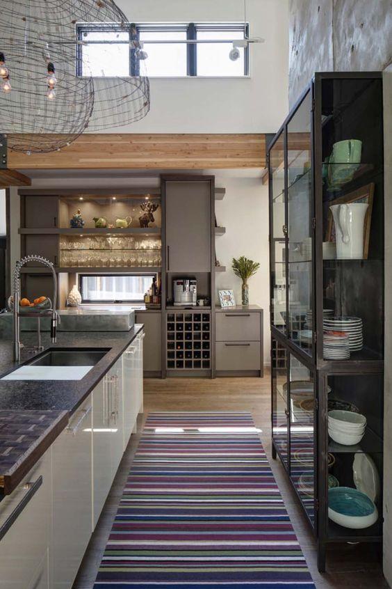una casa moderna con mobili eleganti, travi in legno, finestre a lucernario che portano più luce all'interno di questo spazio dal soffitto alto