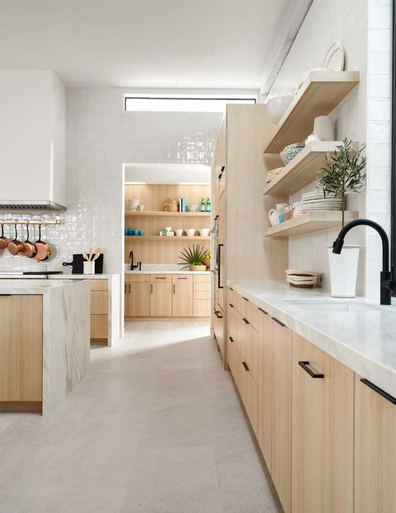 una cucina contemporanea neutra con armadi in legno biondo, piastrelle bianche e ripiani in pietra e una finestra a lucernario