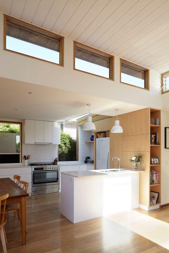 uno spazio neutro moderno con mobili in legno bianco e biondo, finestre usuali e a lucernario per più luce all'interno