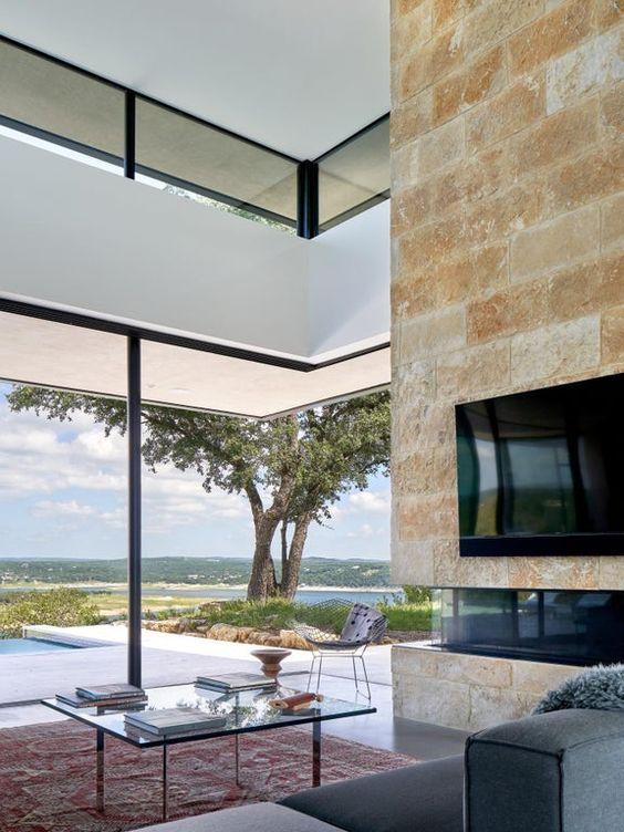 un soggiorno moderno con pareti vetrate per godere della vista e finestre a lucernario che qui portano più luce