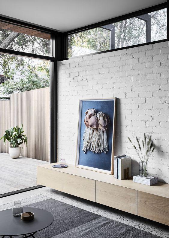 un soggiorno moderno con un muro di mattoni bianchi, una parete vetrata e finestre a lucernario che riempiono lo spazio di più luce