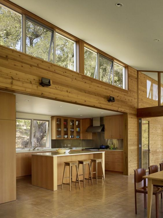 uno spazio tropicale moderno con lucernario e finestre usuali, con rivestimenti in legno alle pareti e mobili in legno