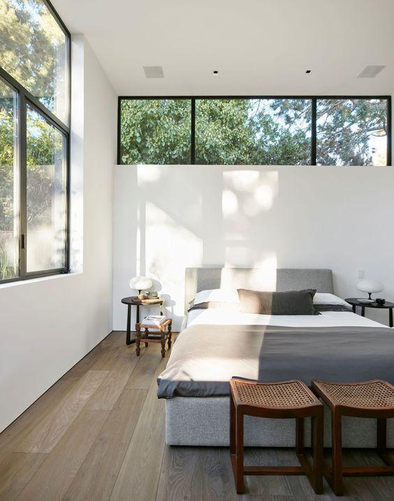 una camera da letto moderna neutra con mobili contemporanei, una grande finestra e una finestra a lucernario sul letto è super chic