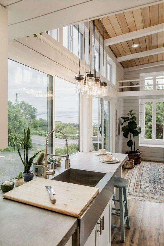 una cucina neutra della fattoria fatta con beadboard, una parete vetrata e finestre a lucernario aggiuntive più piante in vaso
