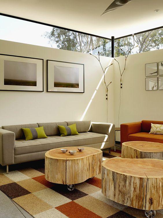 un soggiorno moderno con mobili chic e tavolini da caffè con tronchi d'albero più finestre a lucernario per luce ma privacy