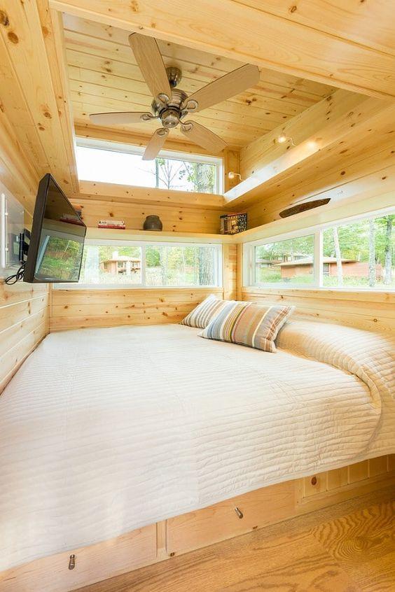 una piccola camera da letto a soppalco rivestita in legno e con piccole finestre a lucernario per inondare lo spazio di luce e godere della vista ma mantenere la privacy