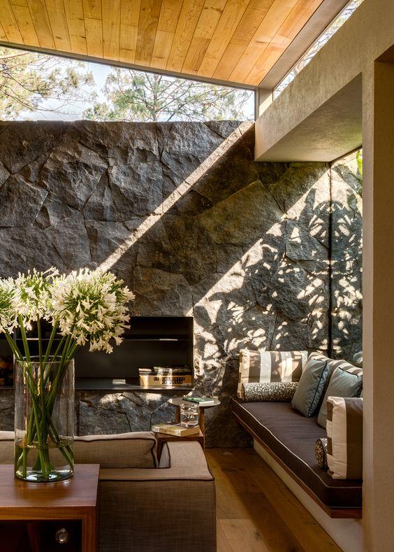 un soggiorno rustico con un muro in pietra, mobili chic, una grande finestra e alcune finestre a lucernario per più luce