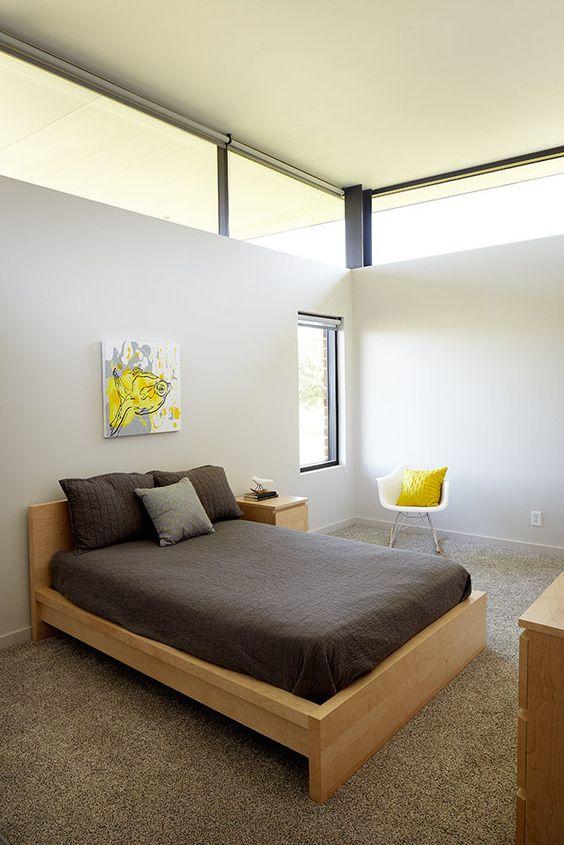 una piccola camera da letto contemporanea per gli ospiti con pareti neutre, mobili in legno biondo, tocchi di giallo brillante e finestre a lucernario per più luce qui