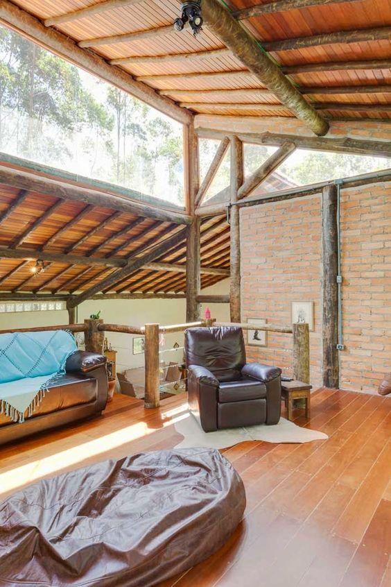 un soggiorno moderno rustico di metà secolo rivestito in mattoni e con alberi grezzi, con finestre a lucernario che brillano di luce