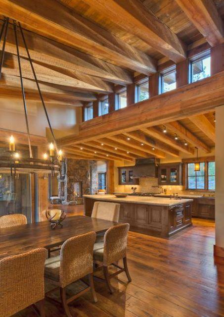 uno spazio rustico con un soffitto inclinato in legno con travi, mobili in legno pesante e luci più finestre a lucernario per più luce all'interno
