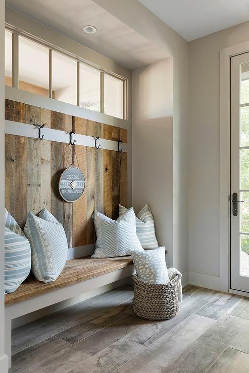 un mudroom rustico con una porta a vetri e una finestra a lucernario per ulteriore luce all'interno è uno spazio accogliente