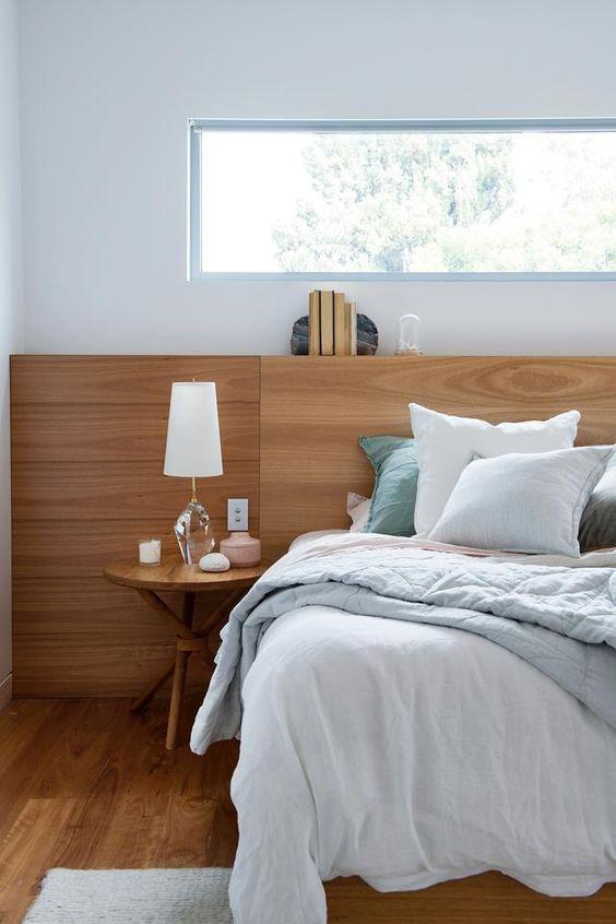 un'elegante camera da letto moderna con molto legno, un letto comodo con lenzuola blu, un tavolo rotondo e una finestra a lucernario per la privacy