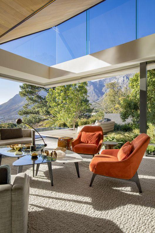 un soggiorno moderno di metà secolo super chic con pareti vetrate e finestre a lucernario, con bei mobili per sedersi e viste meravigliose