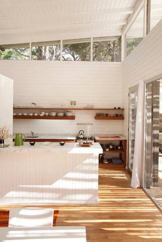 una cucina bianca da fattoria con pareti rivestite di perline e finestre a lucernario che portano luce all'interno e porte scorrevoli
