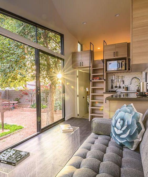 un piccolo spazio neutro con una parete vetrata e finestre a lucernario, con mobili moderni e semplici e una camera da letto soppalcata