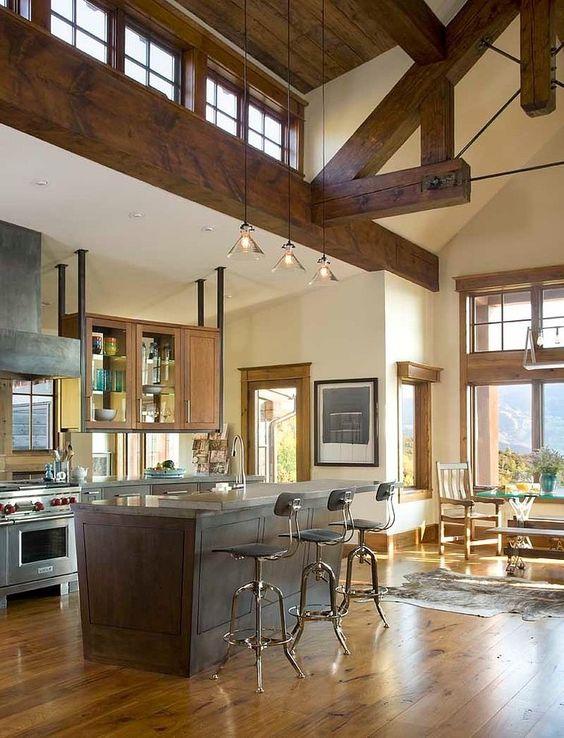 un accogliente spazio rustico con travi in legno tinto, soffitto in legno e lampade a sospensione, grandi finestre usuali e ulteriori lucernari