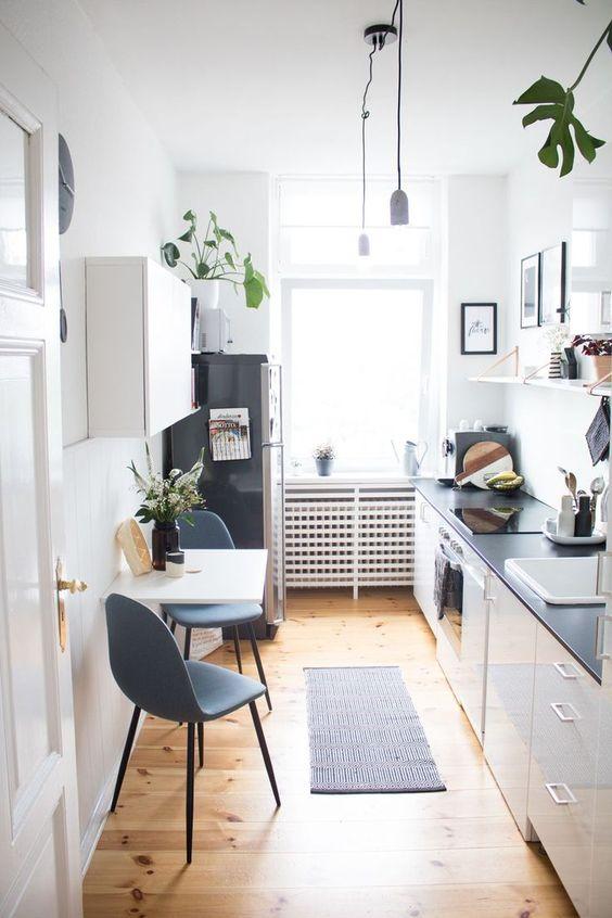 un'elegante cucina moderna bianca con ripiani neri, scaffali aperti, un tavolo pieghevole e sedie grigie più piante