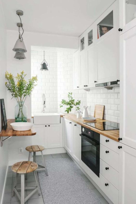 una cucina bianca moderna chic con controsoffitti butcherblock, un tavolo pieghevole e sgabelli e lampade a sospensione vintage