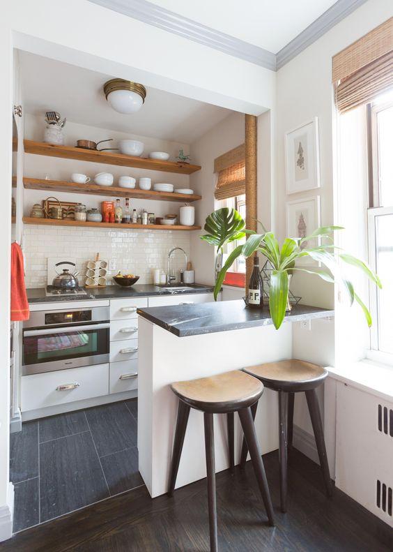 una cucina moderna e chic con armadi bianchi, ripiani neri, scaffali aperti, piante in vaso e sgabelli in legno