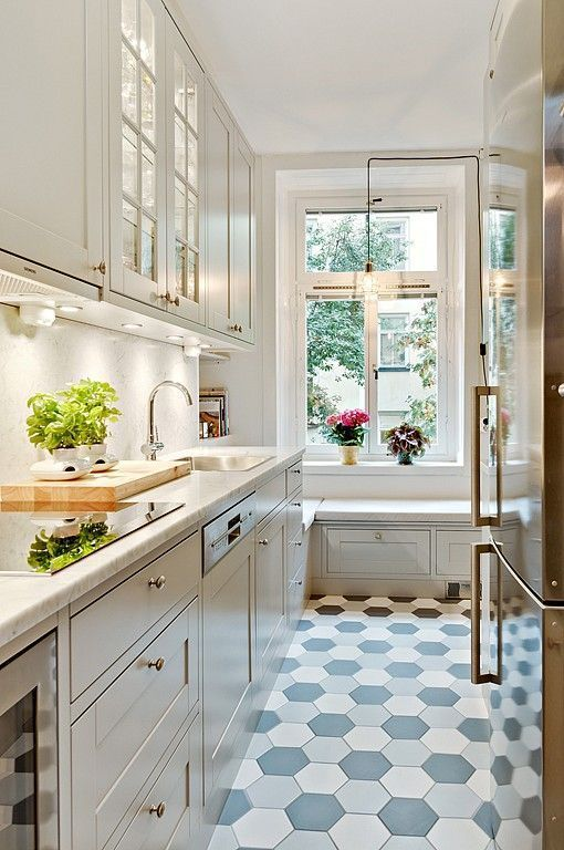 una bella cucina moderna bianca con ripiani bianchi, un paraschizzi bianco, un pavimento piastrellato esagonale e una panca sul davanzale della finestra