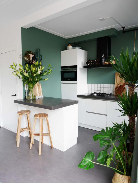 una cucina moderna verde con piastrelle bianche, ripiani in pietra grigia, una cappa nera e piante e fiori in vaso