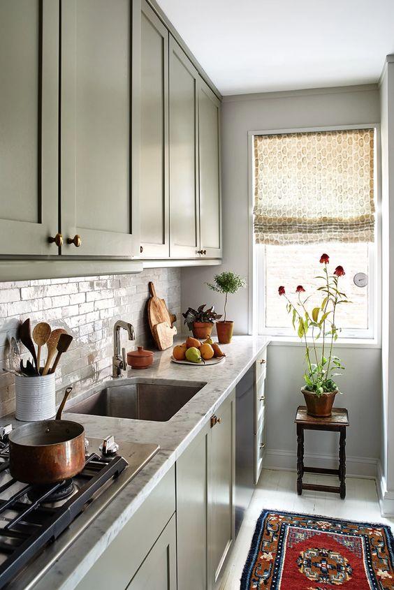 una cucina verde a una parete con ripiani in pietra e un paraschizzi in piastrelle e alcuni tessuti stampati è chic