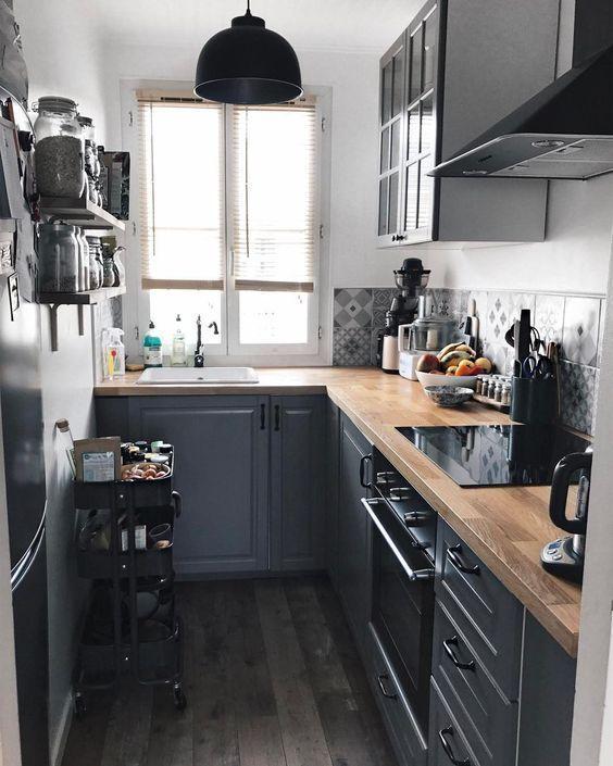 una cucina grigio grafite con controsoffitti butcherblock, un carrello nero e una lampada a sospensione nera e piastrelle stampate grigie