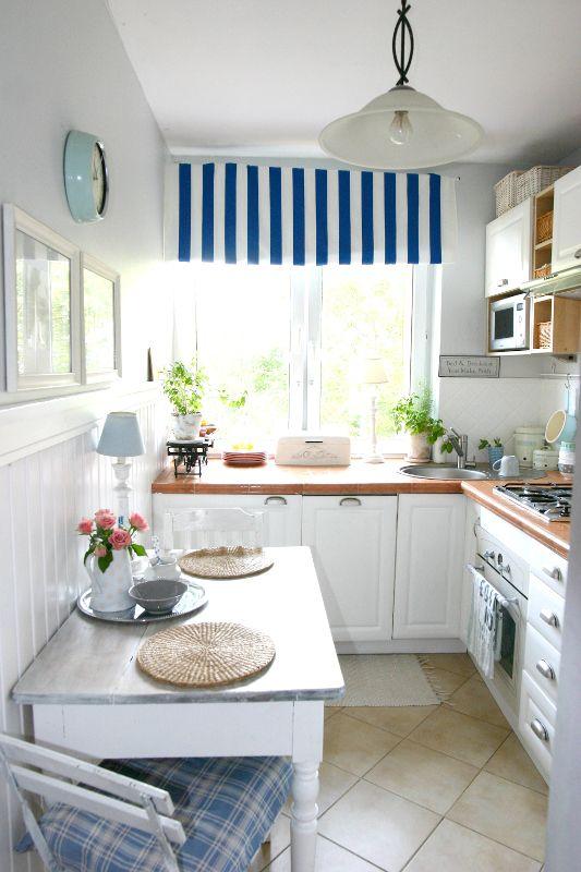 un'accogliente cucina costiera con mobili bianchi, controsoffitti audaci, tessuti a righe e plaid e lampade a sospensione