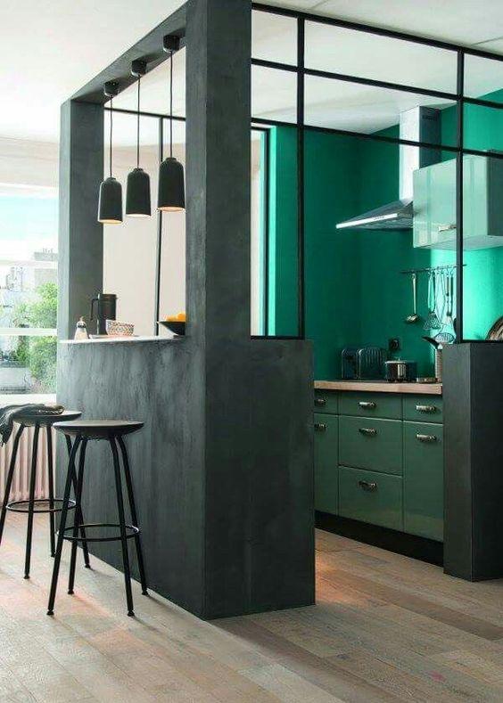 un cubo da cucina moderna verde scuro con pareti e armadietti color smeraldo all'interno, controsoffitti butcherblock e lampade a sospensione