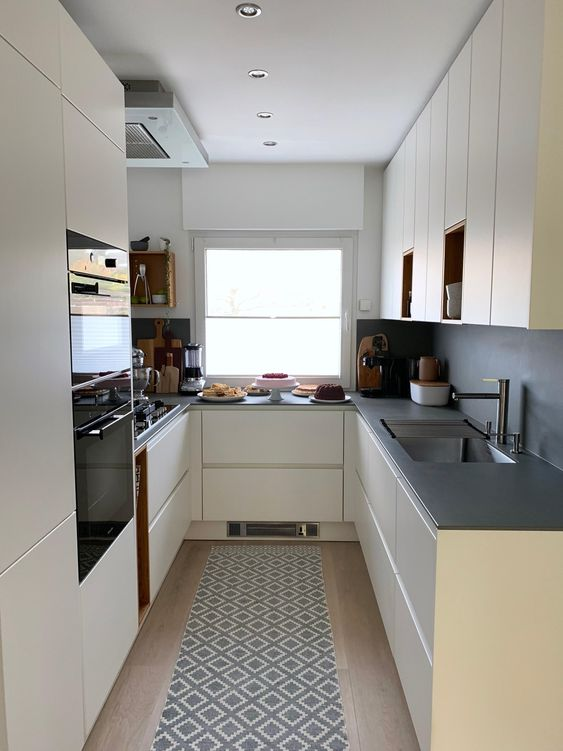 una cucina cremosa ed elegante con un paraschizzi grigio e controsoffitti, elettrodomestici da incasso e una finestra per una vista