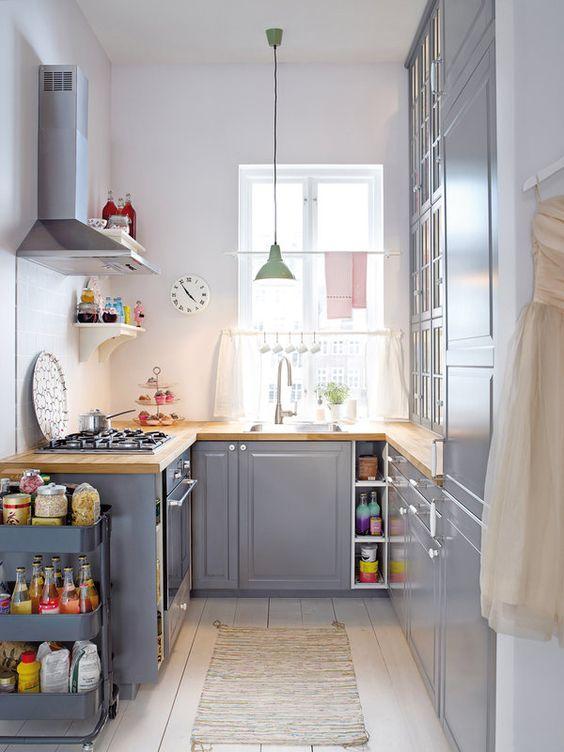 una cucina grigia con controsoffitti butcherblock, una lampada a sospensione pastello e un carrello grigio per spazio aggiuntivo