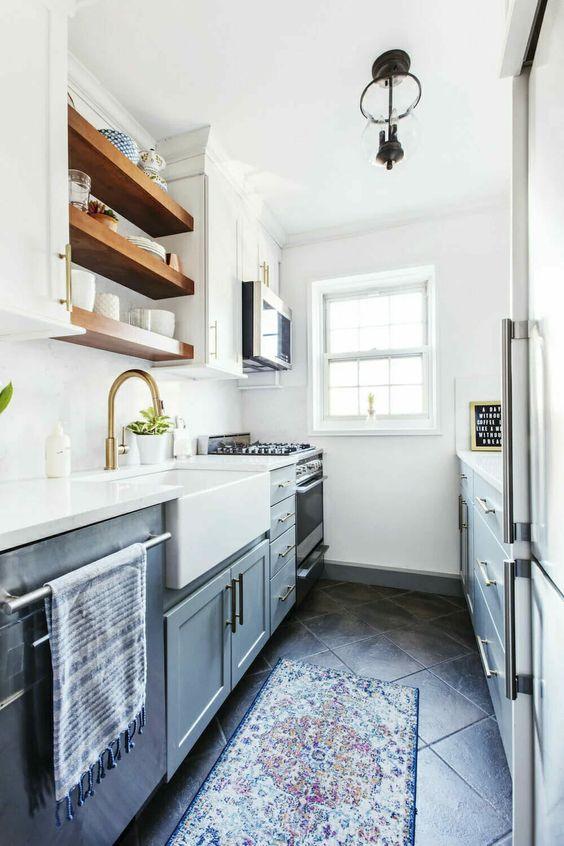 una cucina moderna grigia e bianca con ripiani aperti, tocchi dorati e tappeti stampati è uno spazio fantastico