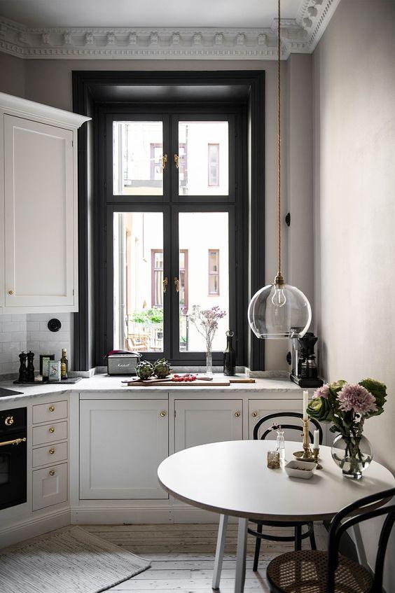 una bella cucina in stile francese in bianco e nero, con sedie raffinate, un tavolo rotondo e tocchi dorati