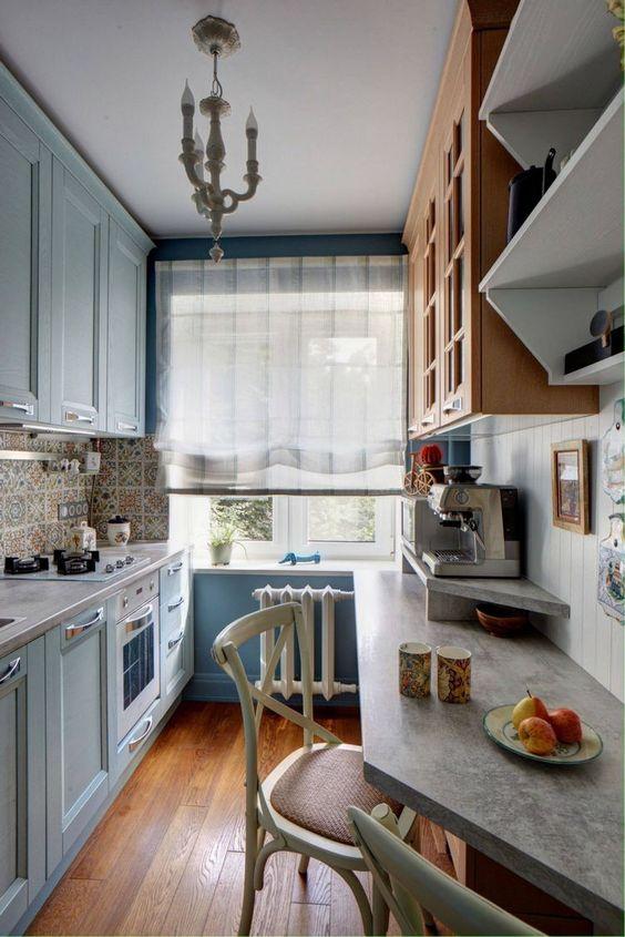una cucina azzurra con pareti blu, armadi colorati e blu, ripiani in cemento e una lampada a sospensione vintage
