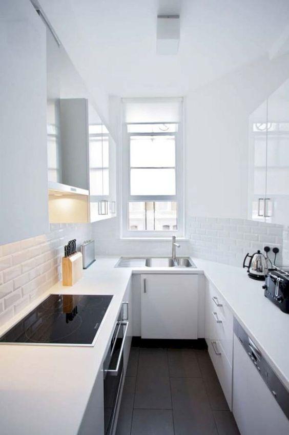 una cucina minimalista completamente bianca con piastrelle bianche sottili, una finestra, elettrodomestici da incasso in nero è puro chic