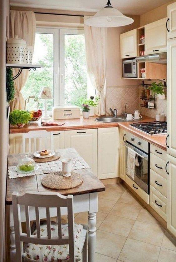 una cucina neutra in stile country francese con un paraschizzi in piastrelle, tessuti neutri, un tavolino e sedie floreali
