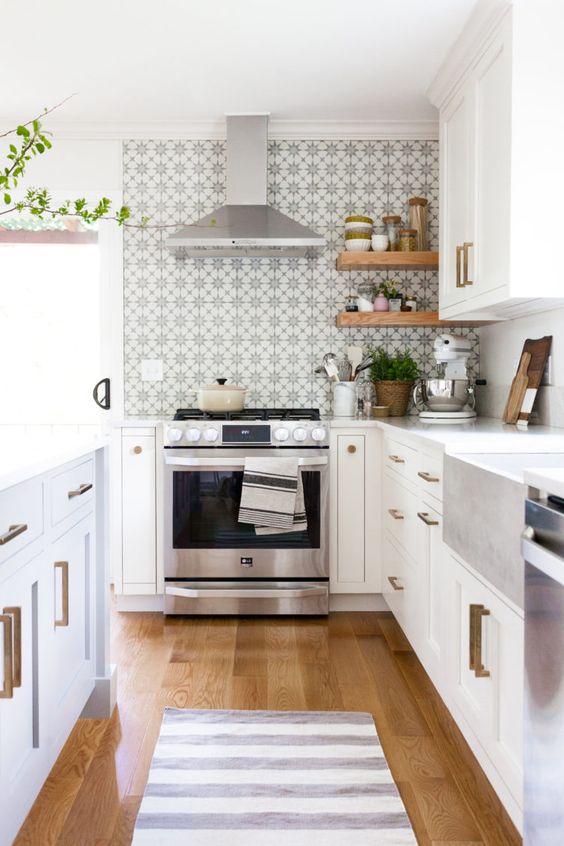 una cucina piuttosto neutra con un paraschizzi in piastrelle stampate, maniglie in ottone, piante in vaso e fioriere intrecciate