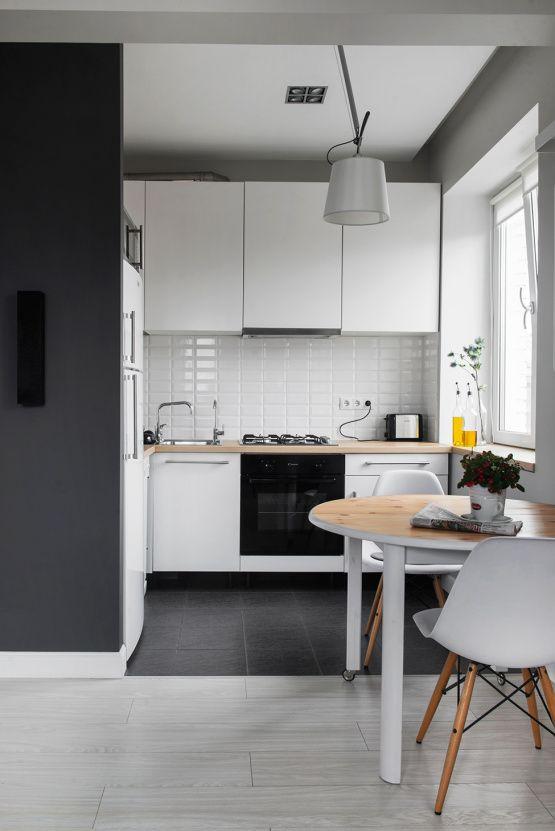 una cucina bianca monocromatica con ripiani in macelleria, un paraschizzi in piastrelle bianche e un tavolo rotondo e sedie
