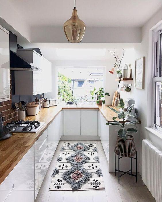 una cucina piuttosto piccola con armadi bianchi, piani di lavoro in muratura, piante in vaso e un tappeto stampato