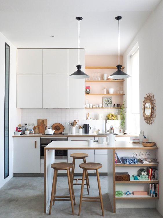 una moderna cucina bianca con ripiani integrati aperti, un'isola cucina con ripiani e lampade a sospensione