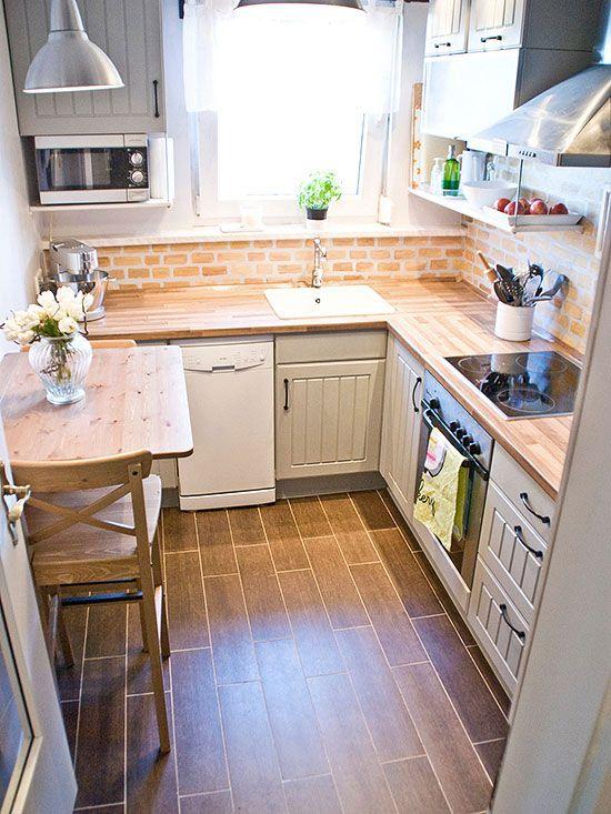 una cucina rustica neutra con controsoffitti in macelleria, un paraschizzi in mattoni rossi e un piccolo tavolo in legno