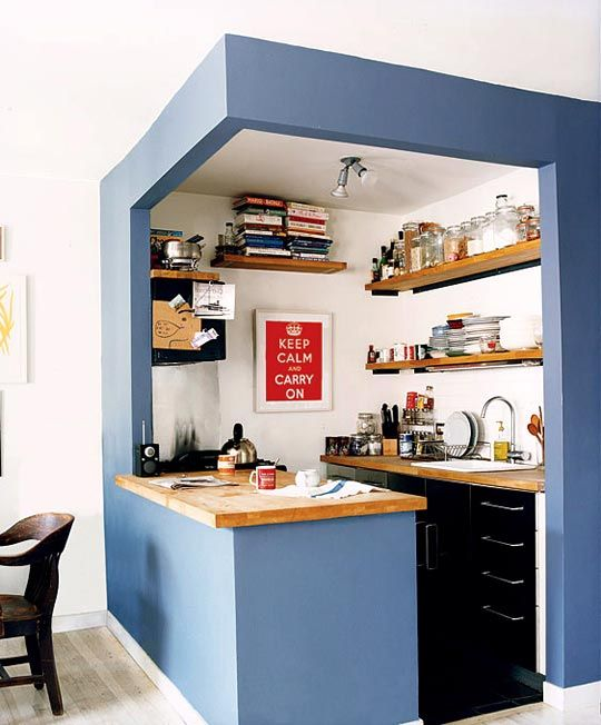 un piccolo cubo da cucina con pareti blu, armadi neri, scaffali aperti e controsoffitti butcherblock è super cool