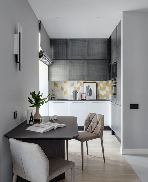 una piccola cucina contemporanea in grigio e bianco, con un backsplash di piastrelle luminose, elettrodomestici da incasso e una zona pranzo accanto