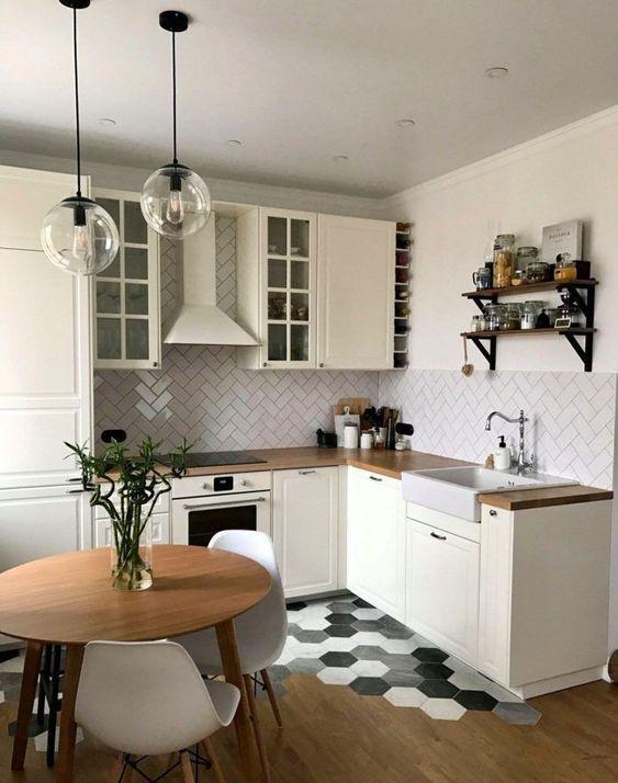 una cucina neutra piccola e chic con controsoffitti butcherblock, un backsplash di piastrelle bianche a spina di pesce, lampade a sospensione e una transizione del pavimento